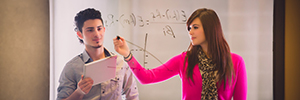 Students analyze research on a whiteboard