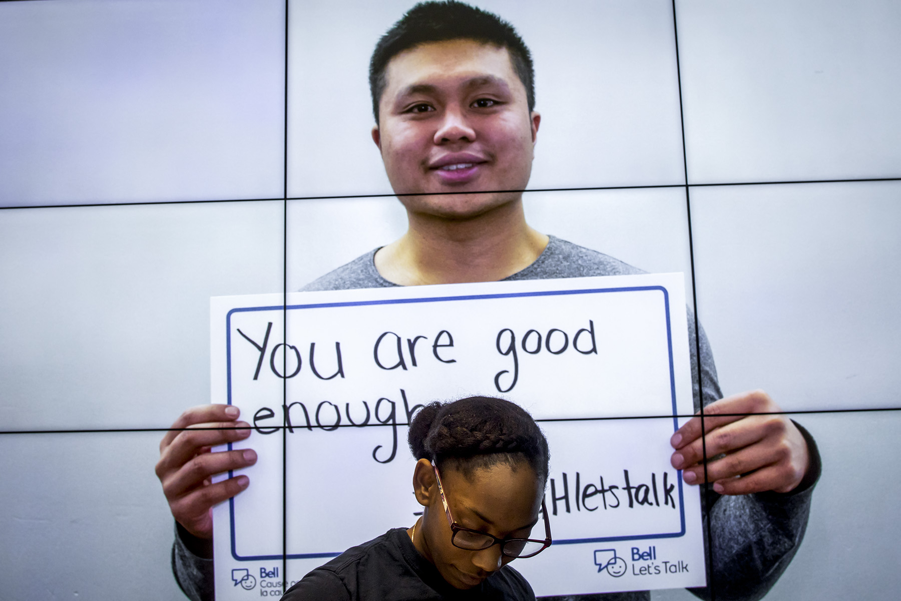 Student holding up a sign that reads: You are good enough