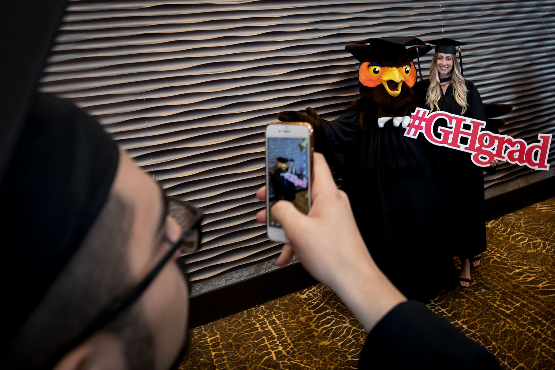 Students pose for photos with UofGH mascot Swoop