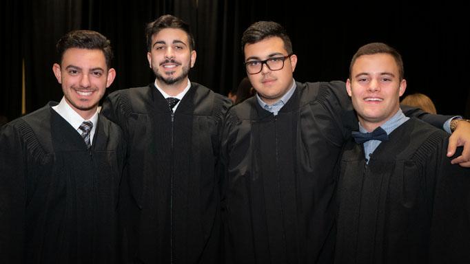 Four graduates hug and pose for a photo
