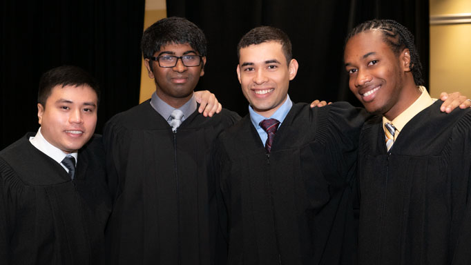 Four graduates hug and smile