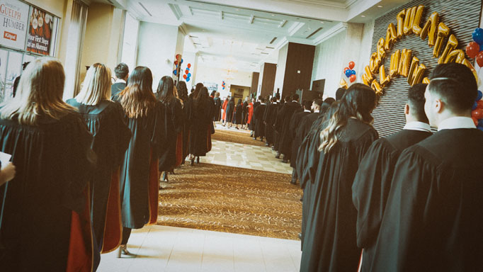A line of graduates wait to enter the hall