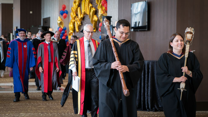 A procession of UofGH leadership approaches the hall
