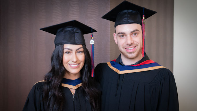 Two smiling graduates pose with their caps
