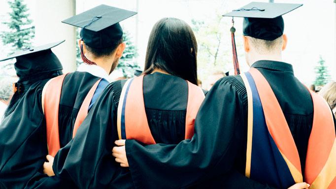 Four graduates facing away from the camera