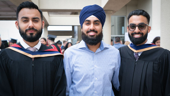 Two graduates pose in their robes