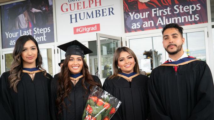 Four graduates smile in a row