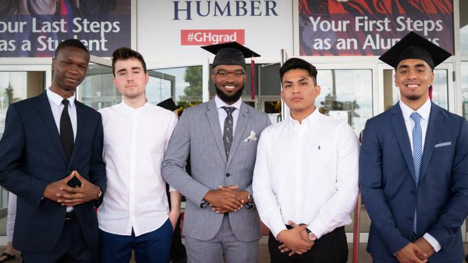 Five graduates pose outside the venue