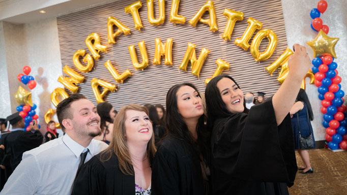 Four graduates pose for a selfie