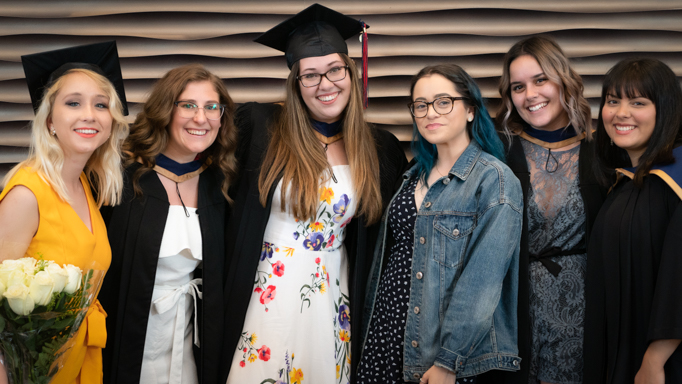 Six students pose with caps and gowns