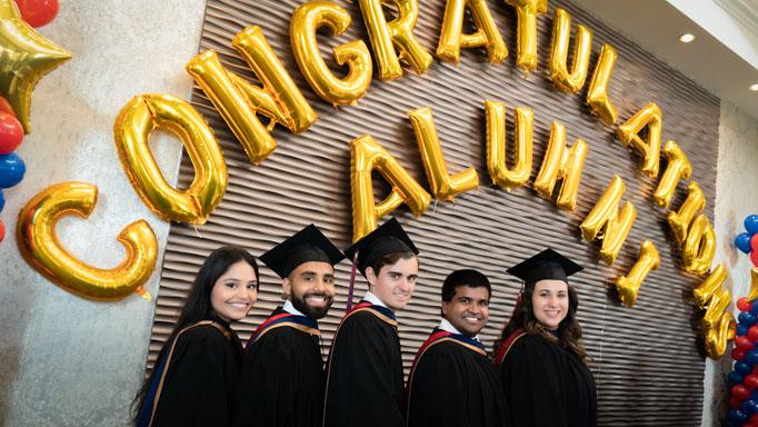 "Five graduates pose in front of a banner reading ""Congratulations Alumni"""