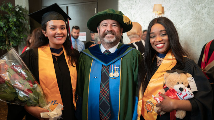 Dr. Glenn Hanna poses with two graduates