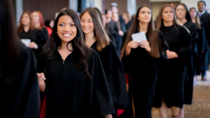 Graduates walk with their credentials
