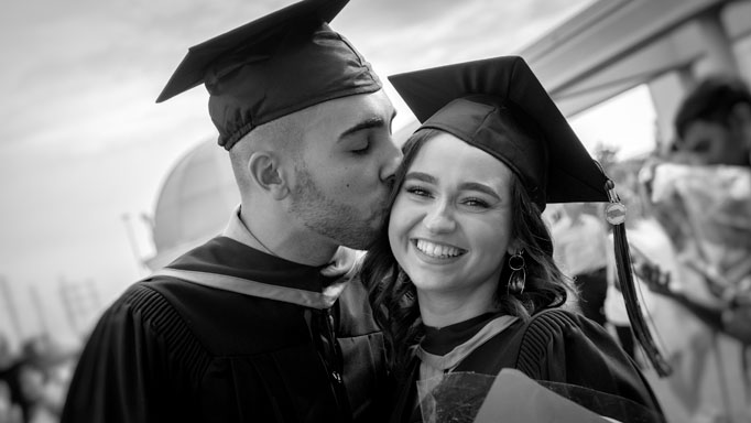 One graduate kisses another on the cheek
