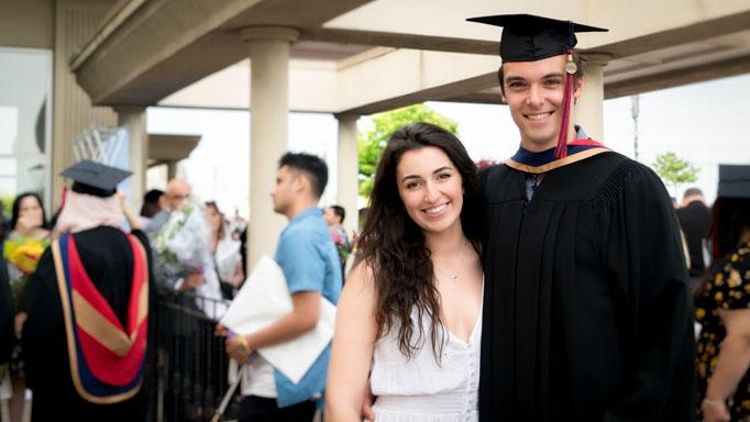 A graduate throws his arm around a friend