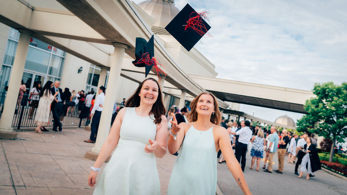 Two graduates toss their caps in the air
