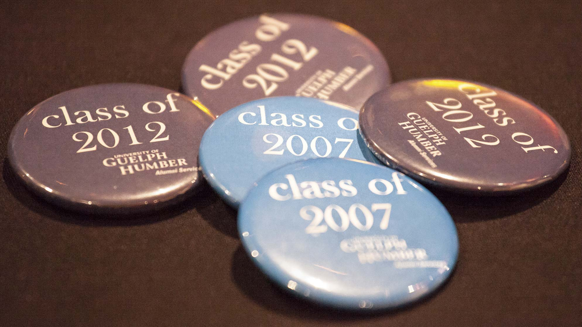 A pile of Class of 2007 and Class of 2012 buttons