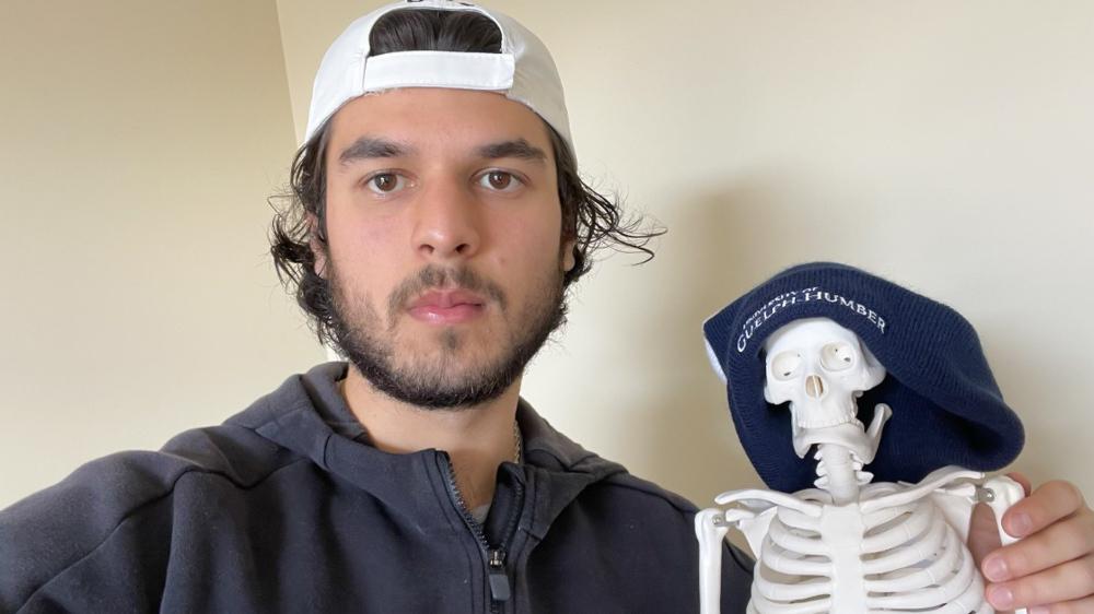 Jaffar Hashimy with a miniature skeleton model