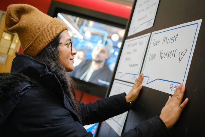 A student posts her handwritten sign on the board