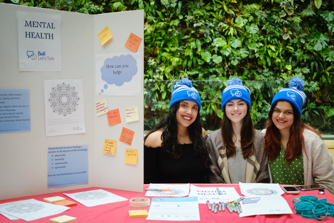 Three students pose next to a poster board with mental health information