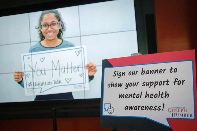"""A student holds up a sign reading """"You Matter"""""""