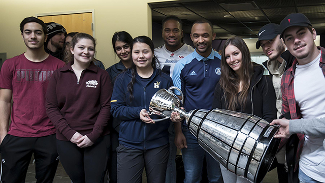 Large group poses with the Grey Cup