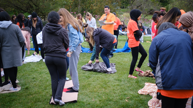 Students stand on folded blankets as Bear Stands Tall leads Blanket Exercise