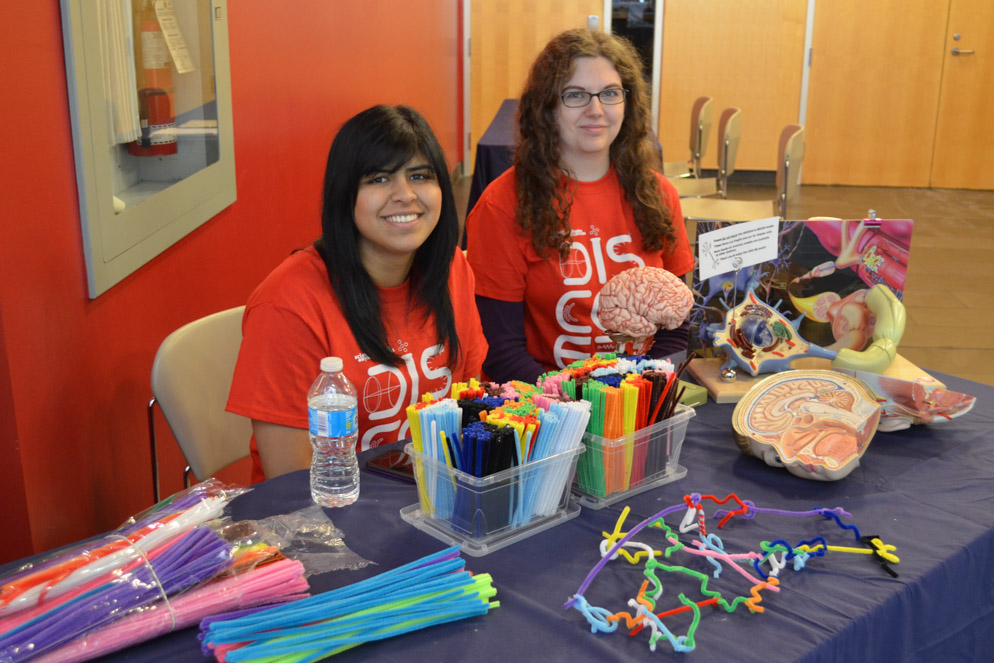 Two smiling student volunteers seated at an activity station