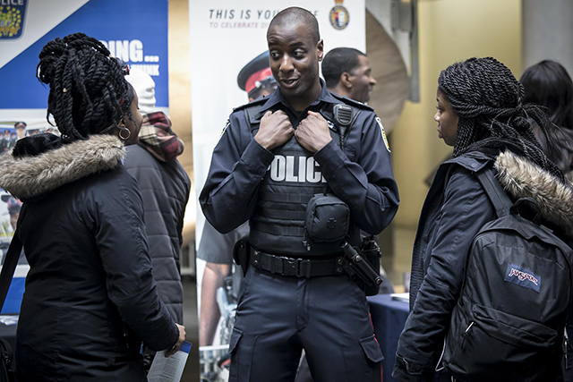 An officer talks to two students