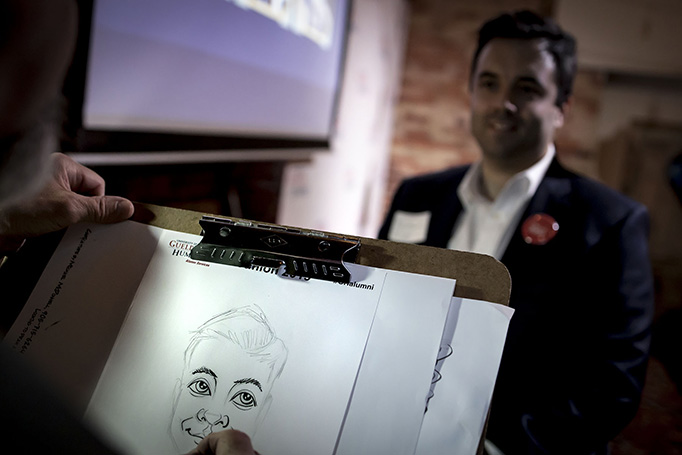 Alumnus poses for a caricature