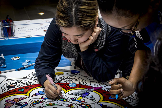 A student signs the mandala