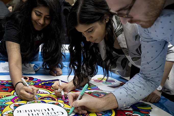Three students sign the mandala