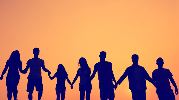 A group of people linking hands in silhouette