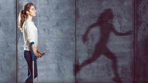 Girl wearing crutches as she looks at a shadow of a female running