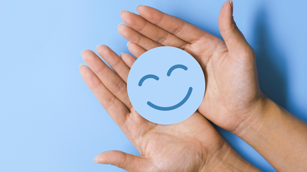 Hands holding a smiley-face emoji