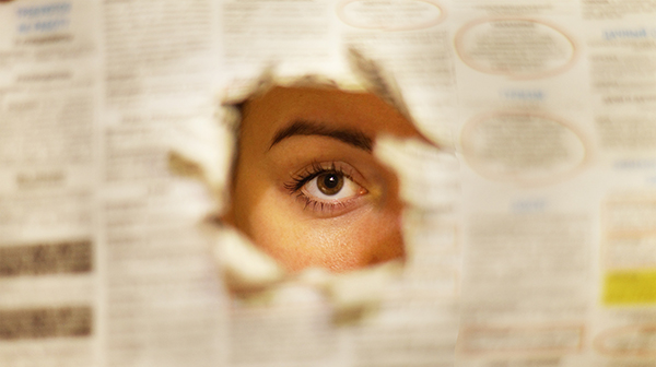 An eye peering through a newspaper