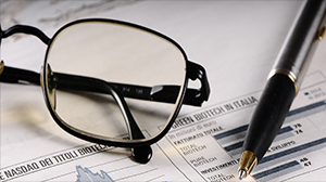 An image of glasses and a pen over the newspaper