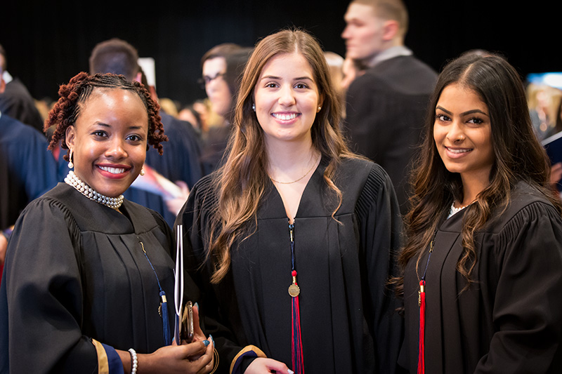 Three students in graduation gowns smiling