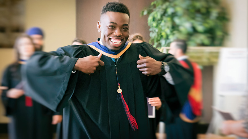 Student in graduation gown smiling