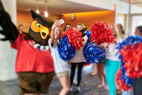 Photo of Swoop and a female student posing for a selfie.