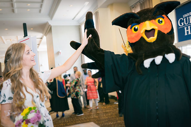 A graduate gives Swoop a high five