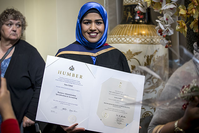 A graduate poses with her degree